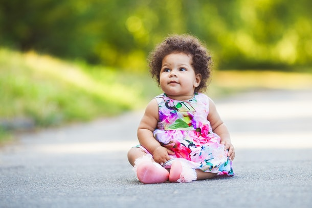Cute and funny little latin girl wearing a colorful flowers dress, outdoors