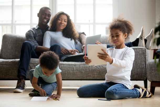 Mixed race children playing drawing with colored pencils on warm floor while happy african parents relax on couch in living room, cute kids siblings having fun at home, black family leisure time