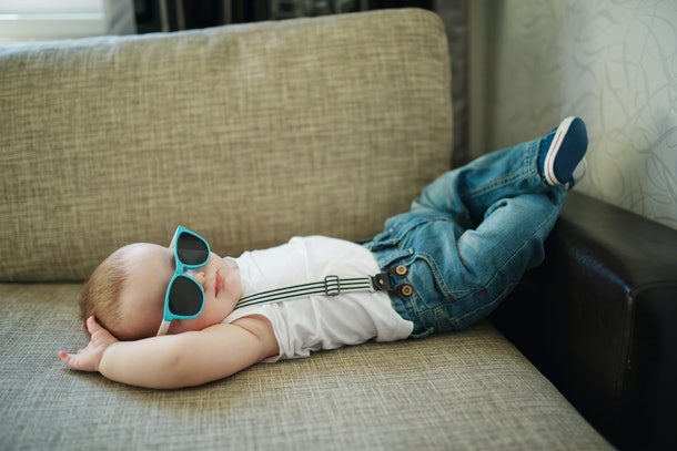 baby lying on couch, wearing sunglasses