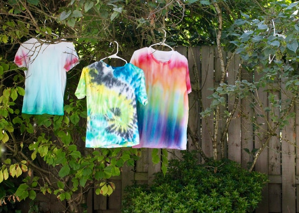tie dye shirts hanging on lilac bush to dry