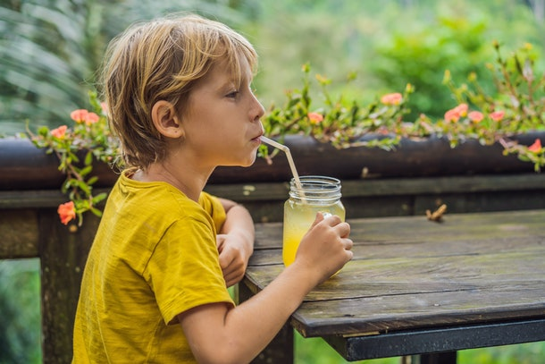 Boy drinking juice in a cafe. What to do with children. Child friendly place
