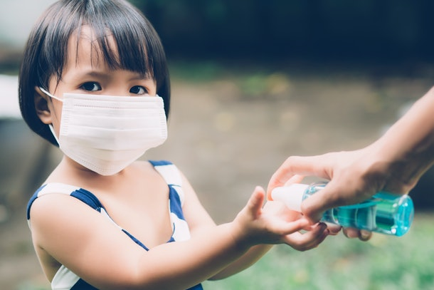 Mother take care son with face mask and sanitizer for protection disease flu or covid-19 outdoors, mom and child wearing medical mask clean hand for safety for outbreak of pandemic in public.